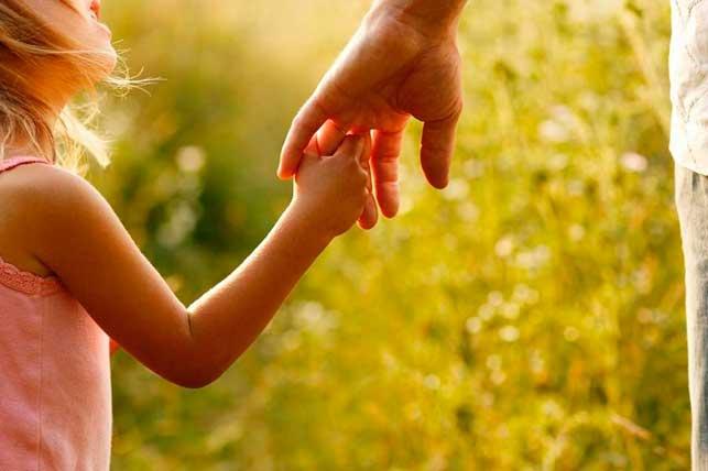 Bambina che tiene fiduciosa la mano del genitore